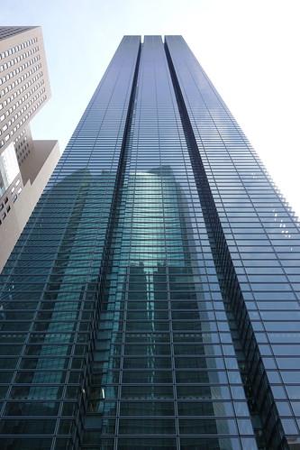 """Shimbashi_3 新橋で撮影した高層ビルディングの写真。 """"日本テレビタワー""""。 全面が緑色掛かったガラス張り。 ガラス面に向かい側の高層ビルディングが映り込んでいる。"""