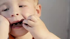 Close-up shot of a little boy eating chocolate
