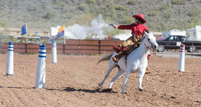 Cowgirl Mounted Shooter Hitting Target