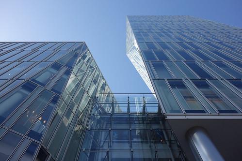 """Aoyama_2 青山通りの """"Ao"""" のビルディングを撮影した写真。 全面ガラス張りで3次元ジオメトリックな外観をしている。"""
