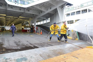 Lt. Sarah Rodino (left), a marine inspector assigned to Coast Guard Sector Puget Sound in Seattle, observes ordinary seamen James Lesh (middle) and Brian Jonsson (right), operate a fire hose aboard Washington State Ferry Puyallup during the ferry's annual certificate of inspection at the Eagle Harbor Maintenance Facility in Bainbridge Island, Wash., Dec. 15, 2014. WSF personnel tested each of the dozens of fire hoses aboard the ferry during the inspection to ensure all nozzles and hoses were in good condition and functioned properly. (U.S. Coast Guard photo by Petty Officer 3rd Class Katelyn Shearer)