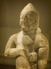 Closeup of Limestone warrior wearing Egyptian kilt and modified Greek helmet Cypriot Archaic 6th century BCE