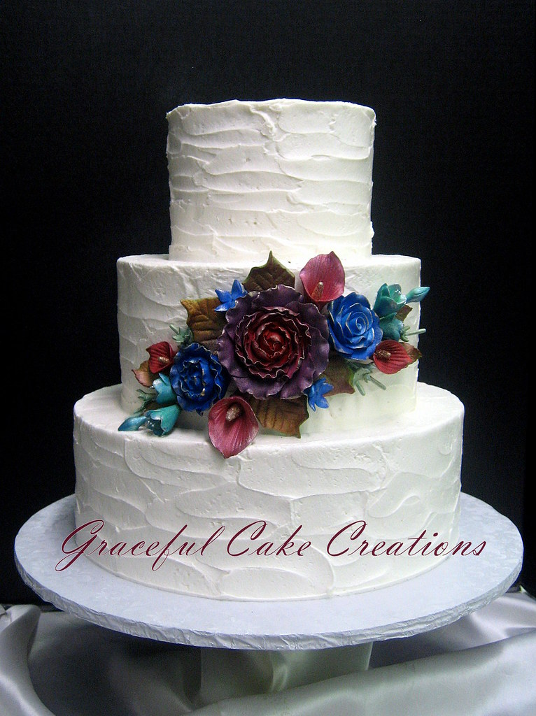 Simple And Elegant Textured Ivory Butter Cream Wedding Cake With A Spray Of Sugar Paste Ranunculas