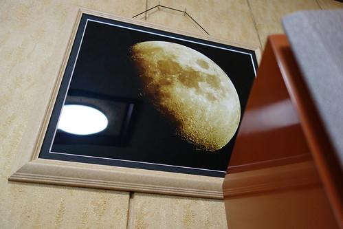 Photo_1 月の写真が額縁に入れられて壁に掛かっている写真。多数のクレーターが写っており漆黒の背景の中に黄色く輝いている。