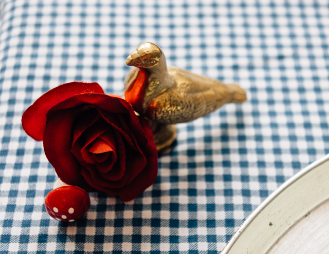 bronze bird and red rose on gingham