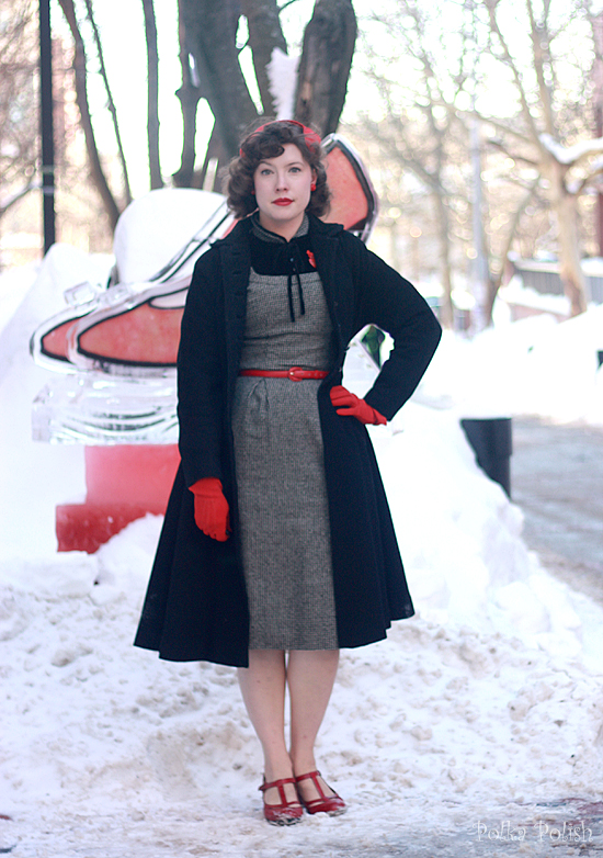 Posing next to an ice sculpure of red high heels wearing red shoes, gloves, and hat with a black 1950s princess coat and a wool dress