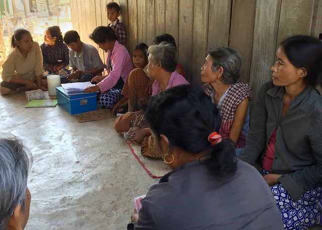 photo: savings group sitting in a circle with a leader reading from a ledger