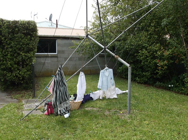 rotating washing line, laden with clothes, fallen on its side due to the centre pole breaking