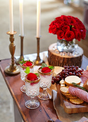 rustic table setting for The Bachelor viewing party with red roses white candles in gold candlesticks cocktails in glasses bread cracker meat and cheese platter and other appetizers