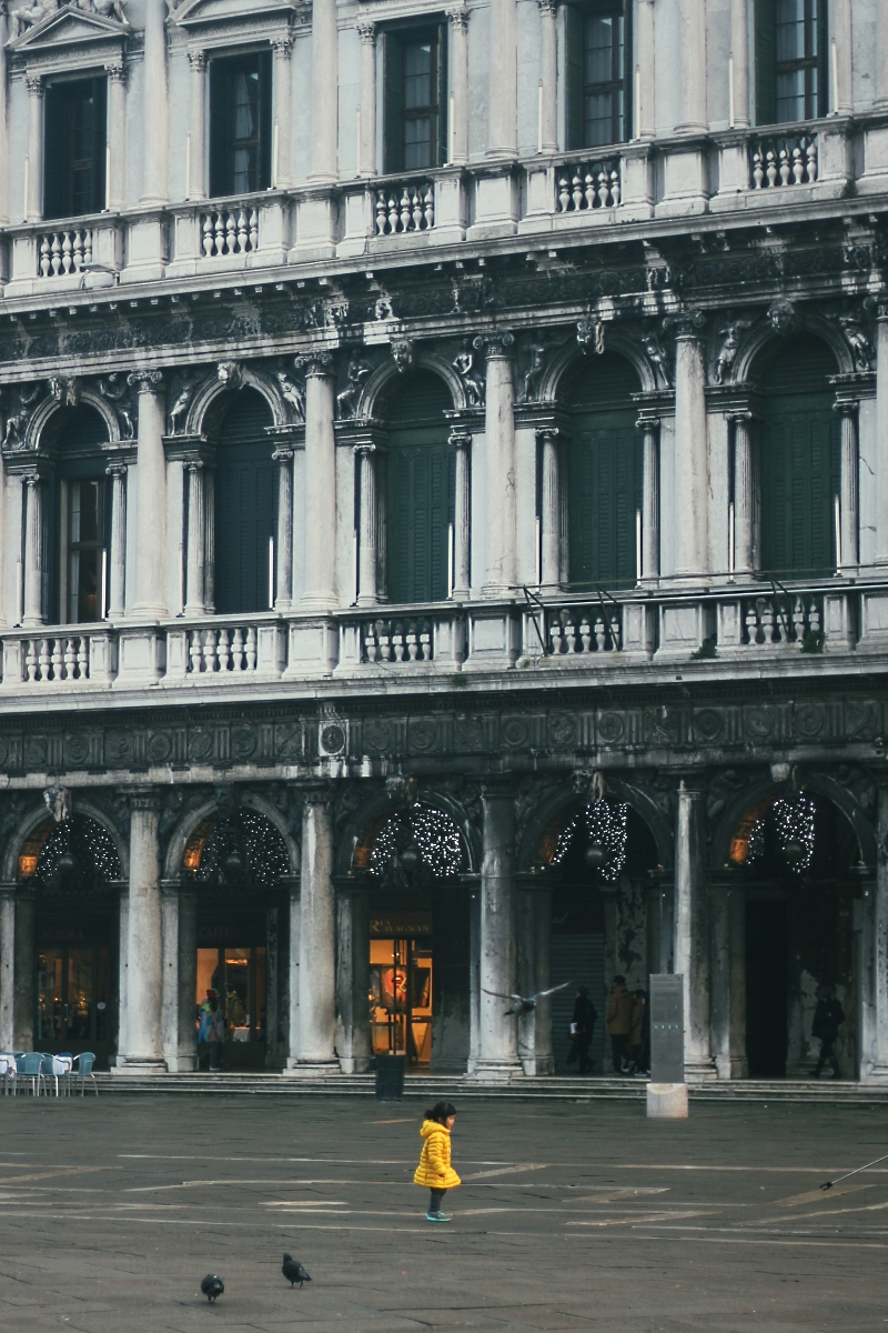 Tiny little girl running in Piazza San Marco