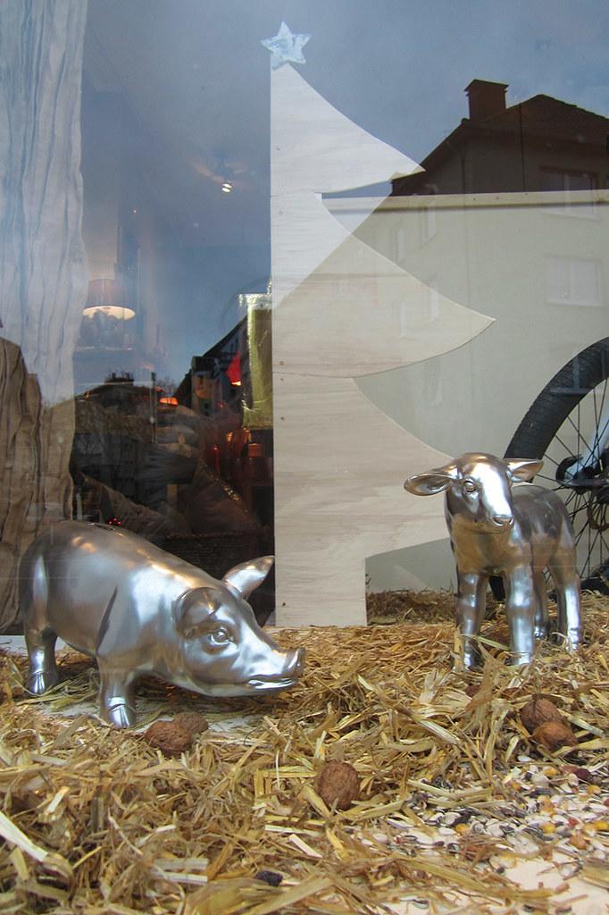 Foto Ein silberfarbiges Schwein und ein Lamm stehen im Stroh in einem Schaufenster