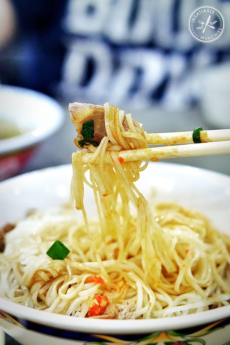Rice noodles getting lifted out of the bowl after being tossed in sauce and chilli