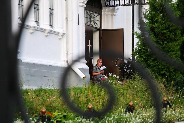 A woman sitting in the premises of Dormition Cathedral, Vladimir, Russia ウラジーミル、ウスペンスキー大聖堂敷地内で読書する女性