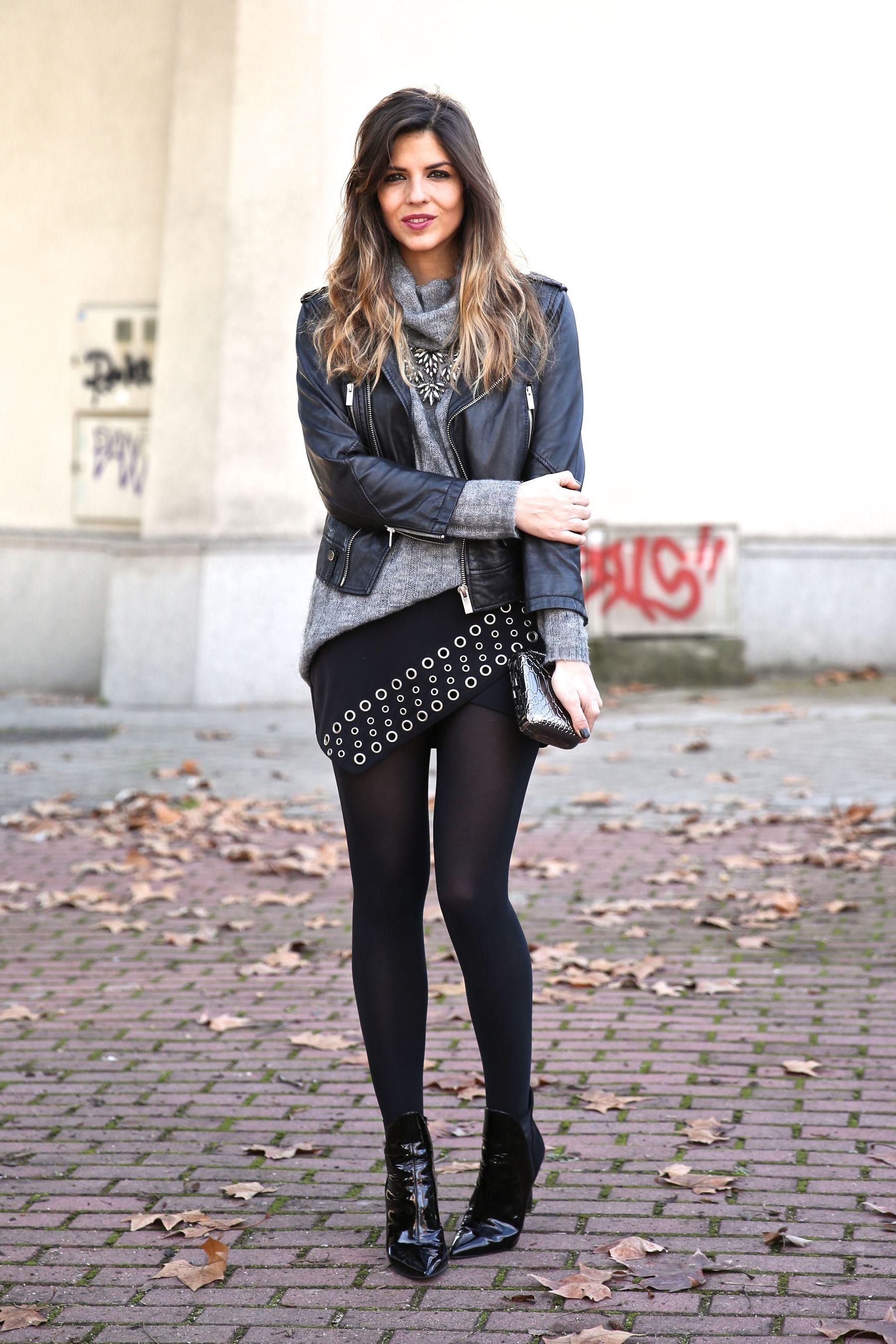 Look chic con chaqueta de cuero, jersey de punto, falda asimétrica negra con detalles metálicos y botines de charol