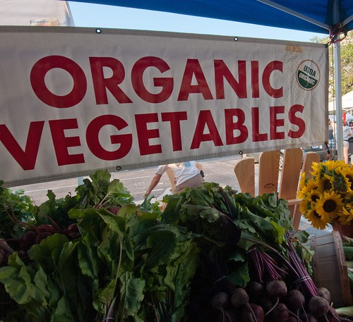 Organic Vegetables sign above vegetables and flowers