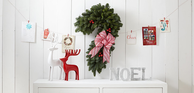 Pine Christmas wreath shaped like a candy cane with a striped bow over reindeer decorations a noel sign on a table and Christmas cards hanging on a string