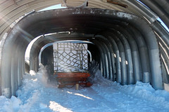Air force pallets (AFPs) of ice rest under an unused steel arch until the next cold deck flight