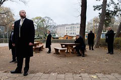U.S. Secretary of State John Kerry, ringed by security guards, speaks with Canadian Foreign Minister John Baird about the status of nuclear program negotiations with Iranian officials as he sits in a park at the scene of the talks, Vienna, Austria, on November 22, 2014. [State Department photo/ Public Domain]