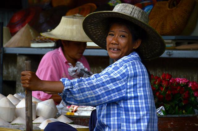 Señora mirando de imprevisto hacia atrás en el mercado flotante mientras sujeta su remo