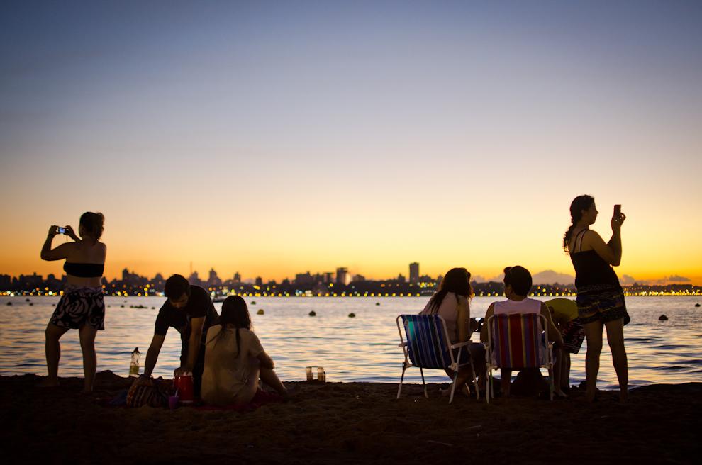 Veraneantes obtienen fotografías de un singular atardecer en la playa San José de la ciudad de Encarnación. El sol se oculta dejando un hermoso crepúsculo sobre la ciudad vecina de Posadas. (Elton Núñez)