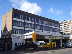 "A four-storey building with a plain, rectangular profile on the top three floors and a protruding canopy on the ground floor.  Signs on the building itself read ""Praise House"" and ""Praise House Church"". while signs on and near the ground-floor canopy read ""Hand Car Wash"" and ""Tyres £5"".  A large pile of tyres can be seen in the forecourt, with an AA van parked next to it."