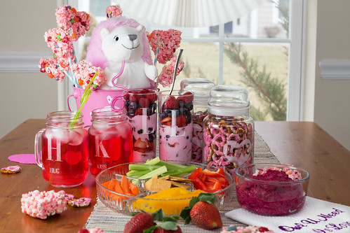 pink Valentine's Day snacks including pink lemonade in mason jar mugs pink beet hummus fresh carrots and pepper vegetables and crackers and marshmallow popcorn and jelly bean treats