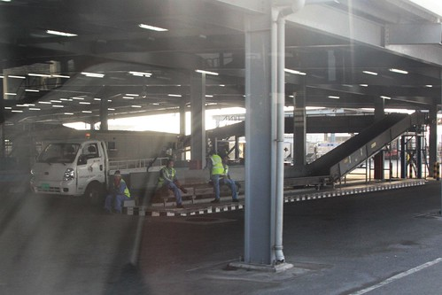Baggage handlers avoid the harsh desert heat