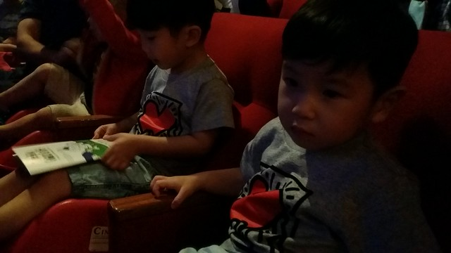 The boys seated in their seats, waiting for the musical to start.