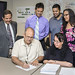 Contract signing between the Laboratory and one of its subcontractors. Shown here: Eric Quintana of the Española-based Performance Maintenance, Inc. adds his signature to provide janitorial equipment and supplies to Los Alamos, while Lorraine Dominguez of the Acquisition Services Management Division's Purchasing group witnesses the signing. From left to right behind Quintana and Dominguez are the Small Business Program Office's Chris Fresquez, the Purchasing group's Nick Perry and Performance Maintenance's Daven Quintana and Geraldine Talachy.