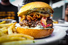 Burger w/ Smoked Gouda Spinach Cream, Bacon, Crispy Onion, and Valentina Hot Sauce - Table 9