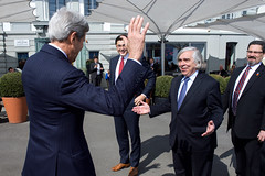 U.S. Secretary of State John Kerry and U.S. Energy Secretary Dr. Ernest Moniz exchange greetings in Lausanne, Switzerland, on March 27, 2015, after bumping into one another on their respective lunch breaks amid negotiations with Iranian leaders about the future of their nuclear program. [State Department photo/ Public Domain]