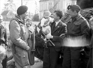 Lieutenant W.J. Trump and Trooper W.H.G. Ritchie of the Fort Garry Horse offering chewing gum to a Dutch child... / Le lieutenant W. J. Trump et le soldat W. H. G. Ritchie, du régiment Fort Garry Horse, offrant de la gomme à mâcher à un enfant hollan