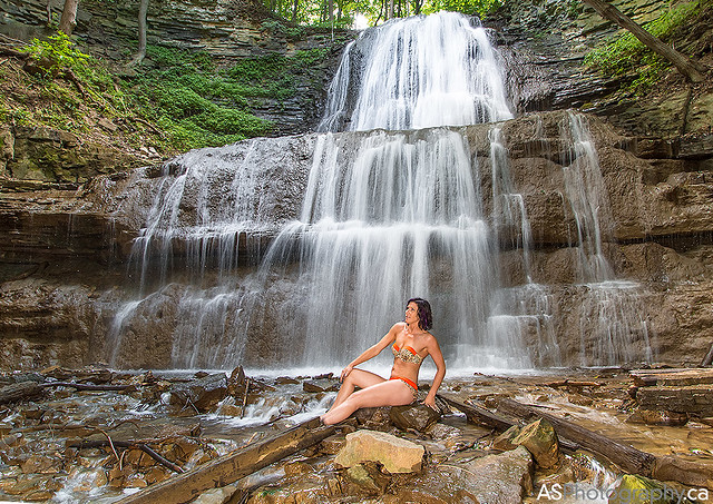Woman in bikini at the base of waterfall
