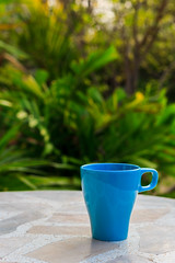 Blue cup on table in morning time.