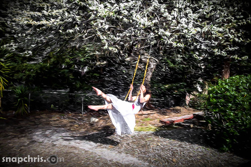 girl swinging in a tree showered by flower petals