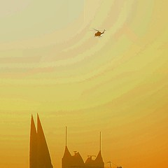 #Bahrain #police #chopper #helicopter #flies in the #even#setting #sun #towers #building #skyline #colour