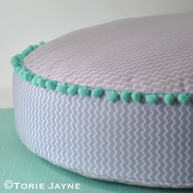 pom pom trim round floor cushion