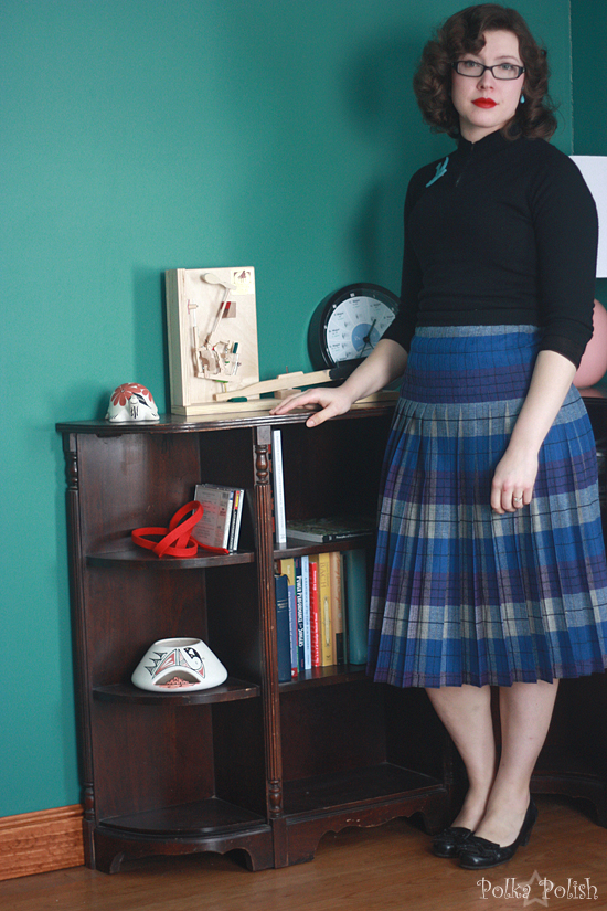 Vintage collegiate style for winter: plaid skirt, black sweater, swallow pin, and loafer pumps