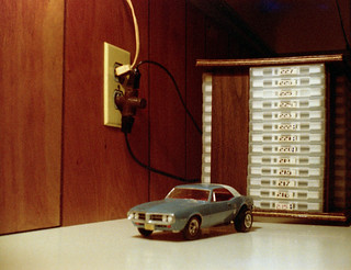Still life in my room with a rack of cassette tapes and a customized plastic model of a 1967 Pontiac Firebird with fat slicks in the rear. Milford Connecticut. June 1977.