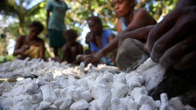 Breaking coral for lime, Solomon Islands. Photo by Wade Fairley