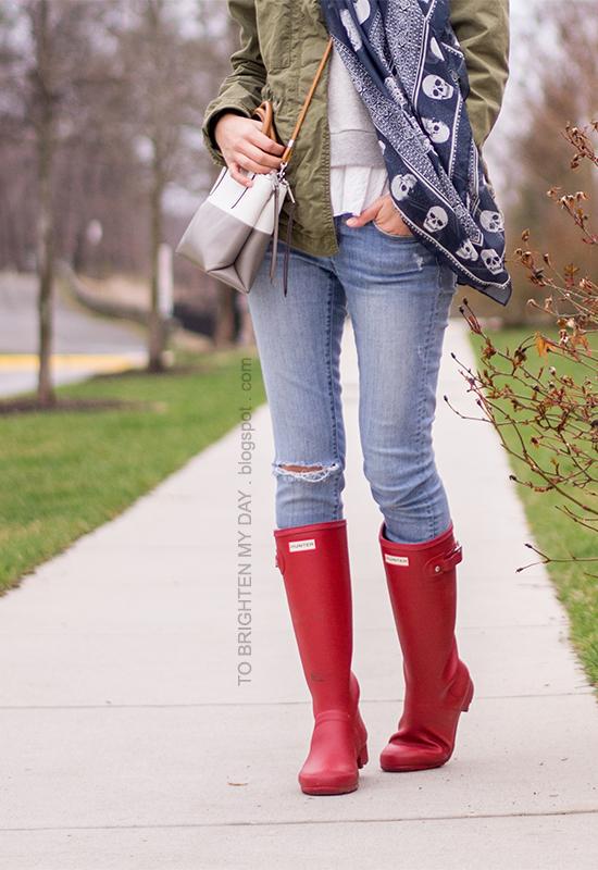 green military  jacket, navy printed scarf, gray ruffled sweatshirt, red rain boots