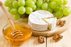 Still life of cheese, honey, walnuts and grapes