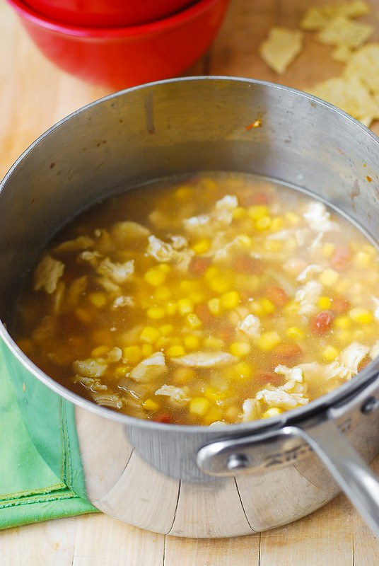 adding corn to the beans and chicken for the chili