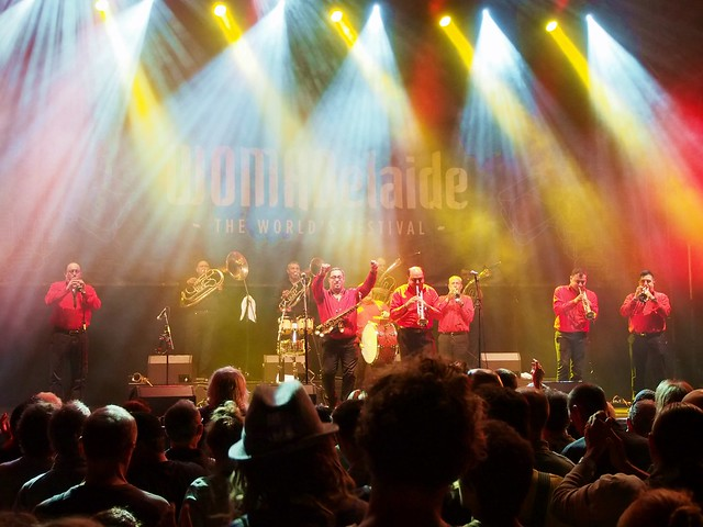 The members of Fanfare Ciocarlia, most playing brass instruments, bathed in bright colourful stage light.