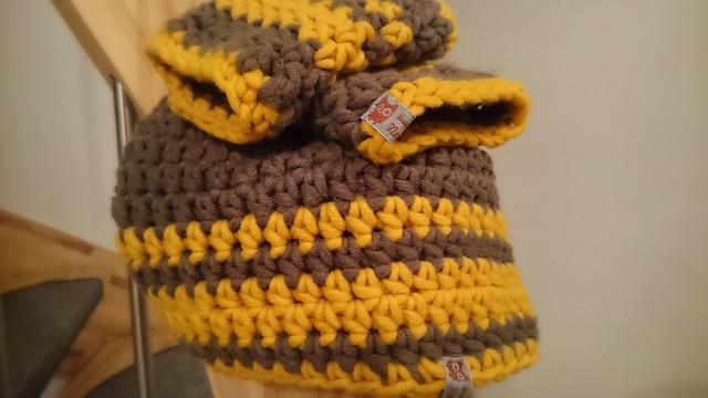 Die fertige Mütze und die Stulpen sind grau mit gelben Streifen.