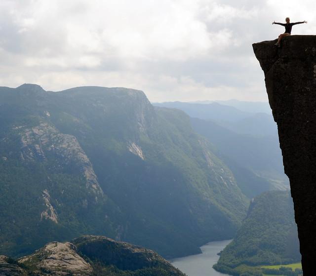 Sentada y saludando con los brazos abiertos desde el borde del Púlpito en los fiordos de Noruega