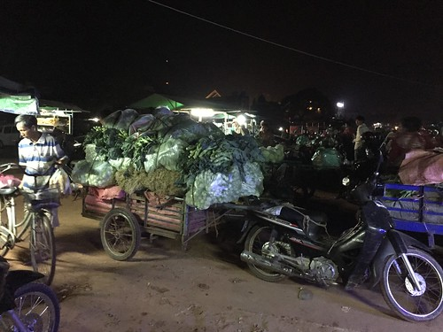 photo: motorcycle with trailer piled high with bags of vegetables