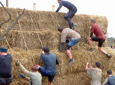 Mike (in the middle) climbing over hay bales Image