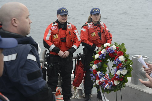 Chief Petty Officer Brandon Alani, a boatswain's mate assigned to Coast Guard Maritime Safety and Security Team 91101 in Seattle, Fireman Levi Stubblefield and Seaman Jaclyn Carricato, from Coast Guard Station Seattle, look on during an at-sea wreath laying in honor of Petty Officer 3rd Class Ronald Gill Jr. near Vashon Island, Wash., March 25, 2015. Chris Magavero, retired Coast Guard chief petty officer and Gill's lead petty officer while stationed at the MSST 91111 in Anchorage, Alaska, spoke of his time serving with Gill and reminded crew members of the dangers of the job. (U.S. Coast Guard photo by Petty Officer 3rd Class Amanda Norcross)