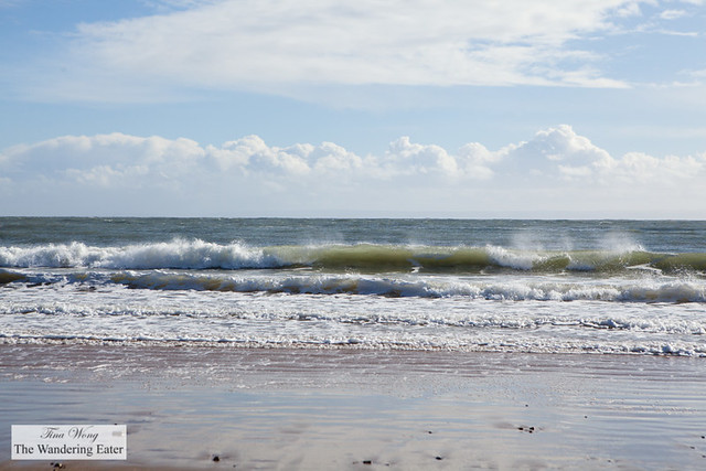 Rolling waves and puffy clouds on Langland Bay in Swansea, UK